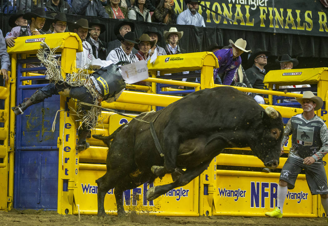 Stetson Wright of Milford, Utah, clings to the gate after being thrown from Pickup Man in Bull ...