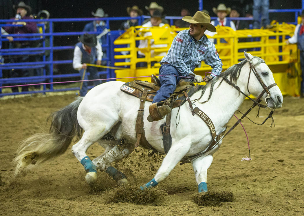 Header Clay Smith of Broken Bow, Okla., looks back after roping a steer during Team Roping at t ...