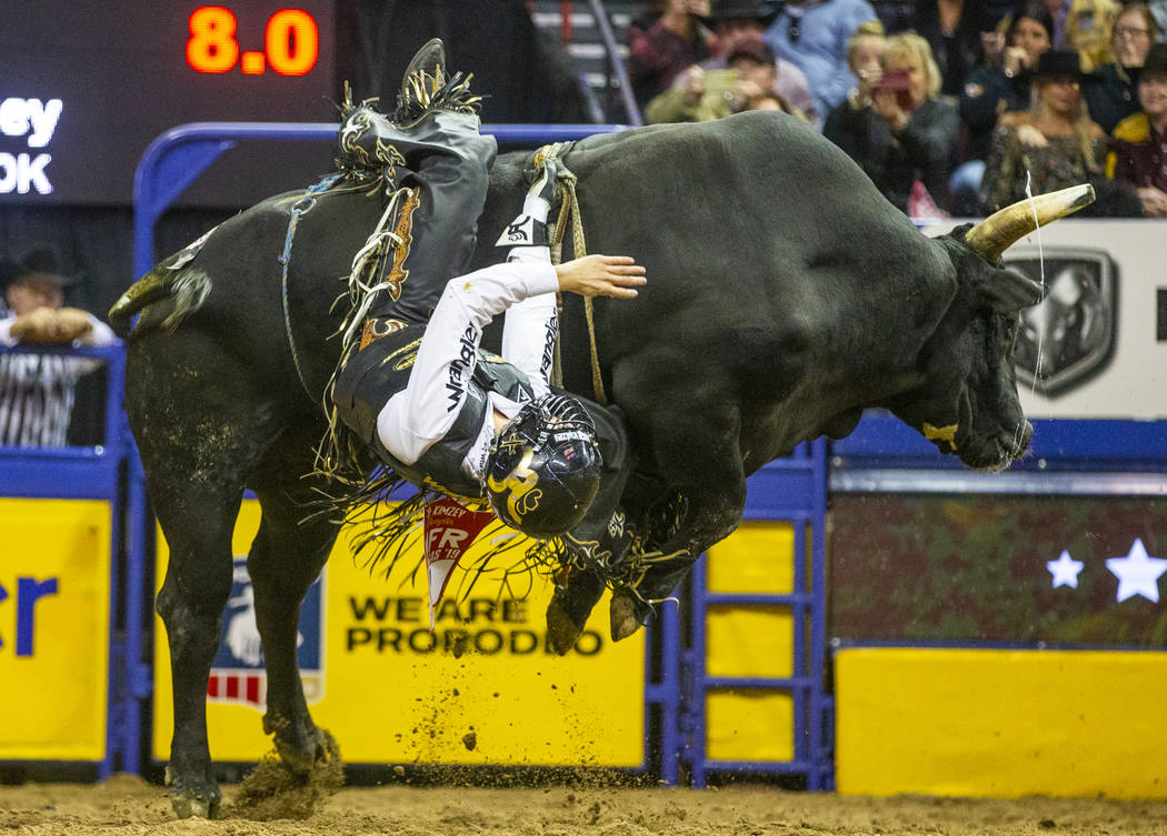 Sage Kimzey of Strong City, Okla, hangs on as he rides River Monster in Bull Riding during the ...