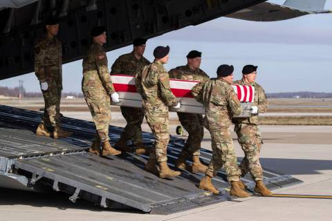 An Army carry team moves a transfer case containing the remains of U.S. Army Sgt. 1st Class Mic ...