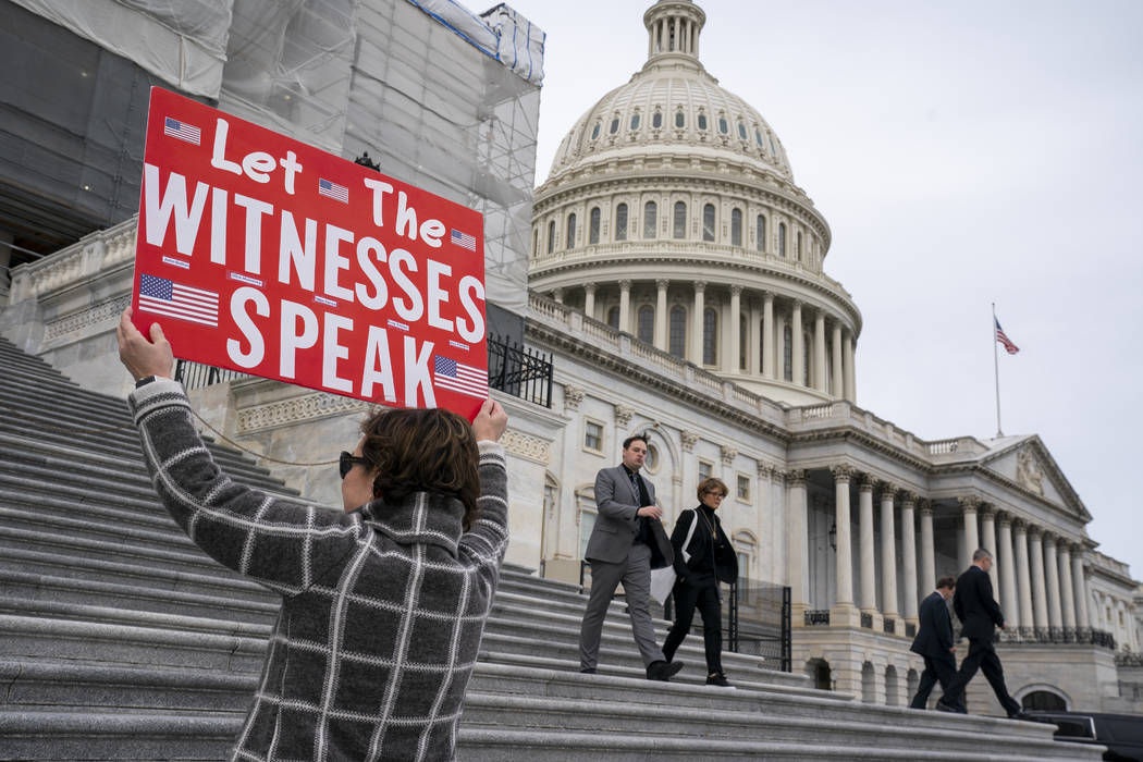 Laura Albinson of Pasadena, Md., displays a message for members of the House as they leave the ...
