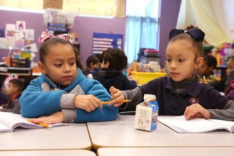 E'liana Trujillo borrows a pencil from Maryah Villezcas in Shamika Abbott's first grade class a ...