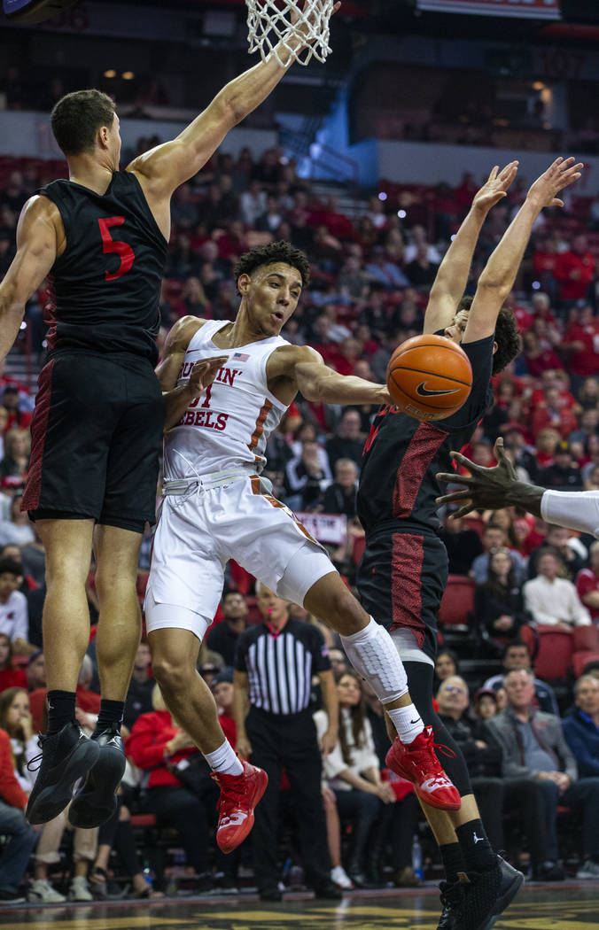UNLV Rebels guard Marvin Coleman (31, center) gets off a pass between San Diego State Aztecs fo ...