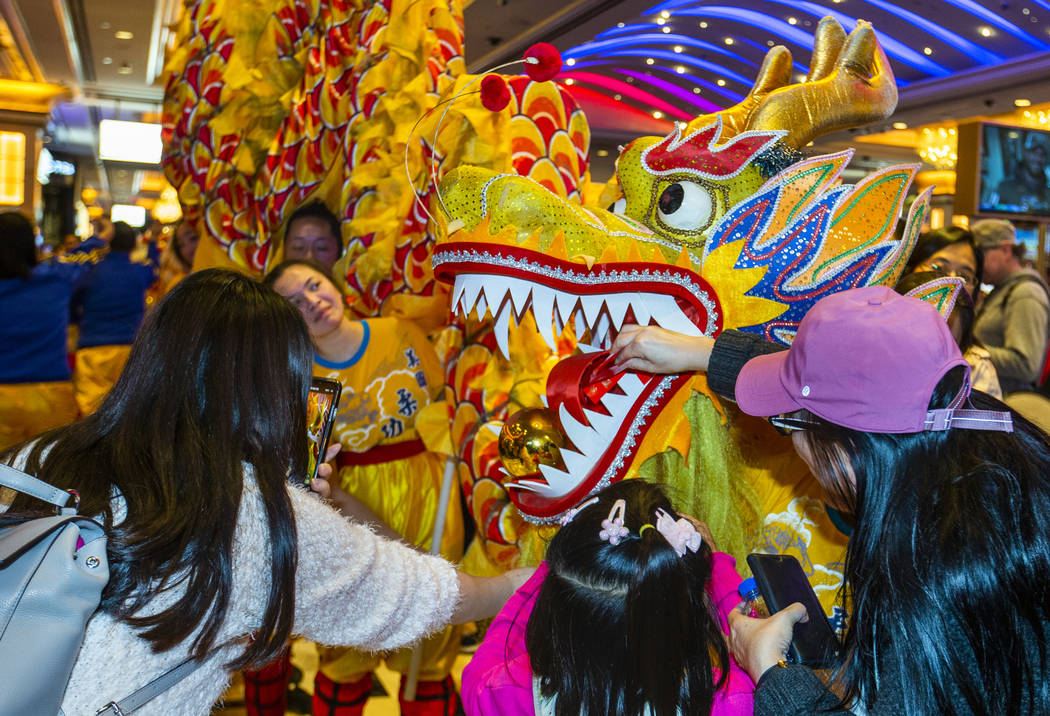 People place money into the mouth of a dragon for good fortune as dancers from the Yau Kung Moo ...