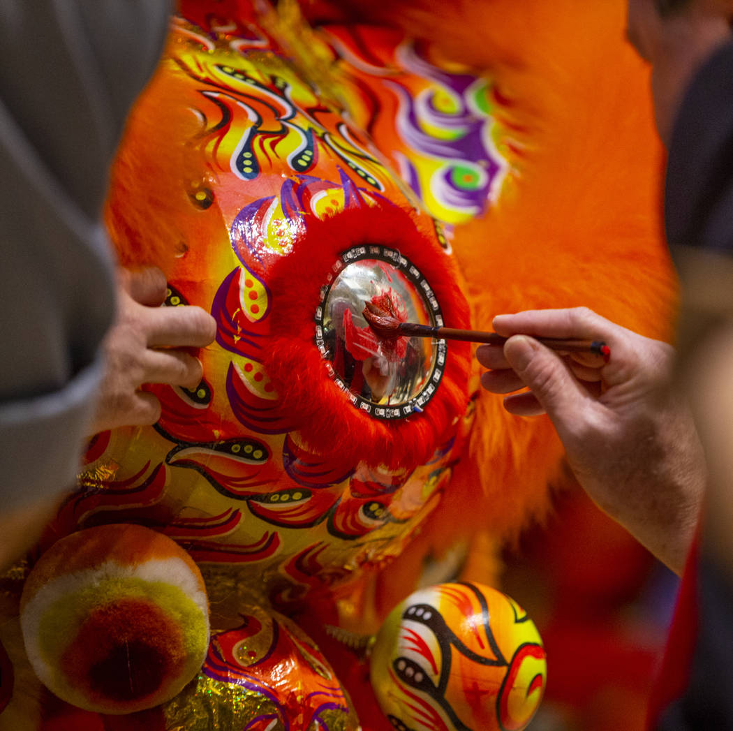 The Lohan School of Shaolin help paint the lions as they ready for a lion dance as the Grand Ca ...
