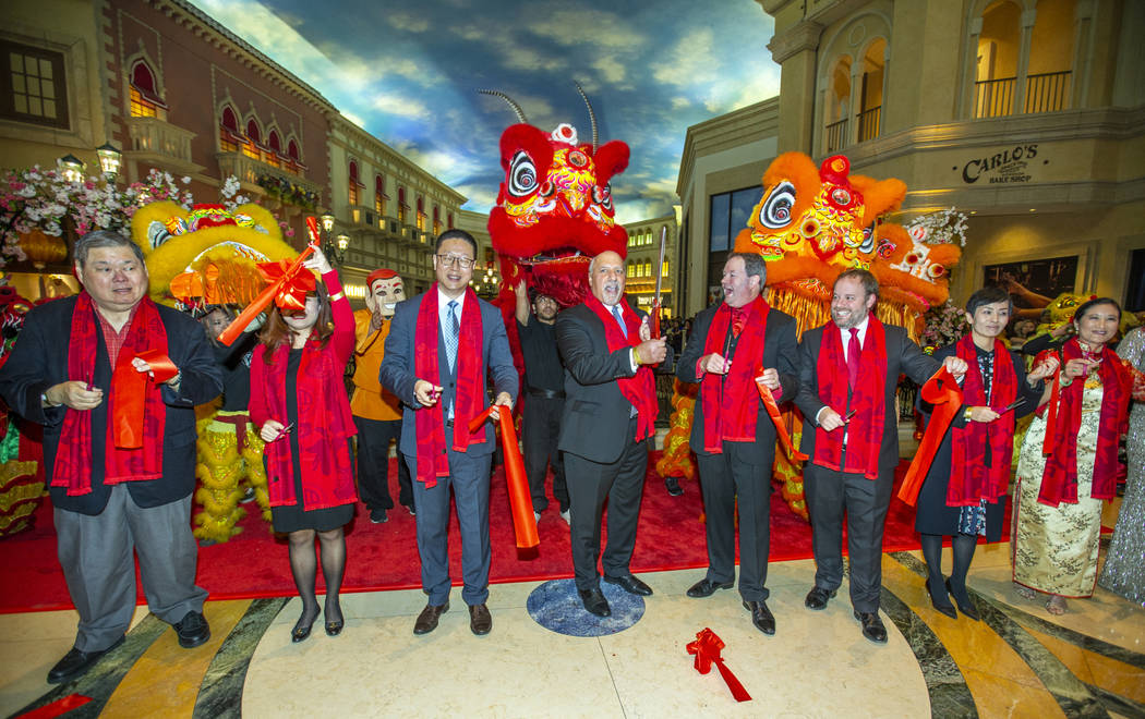 Invited dignitaries cut a ribbon to officially start as the Grand Canal Shoppes celebrate the Y ...