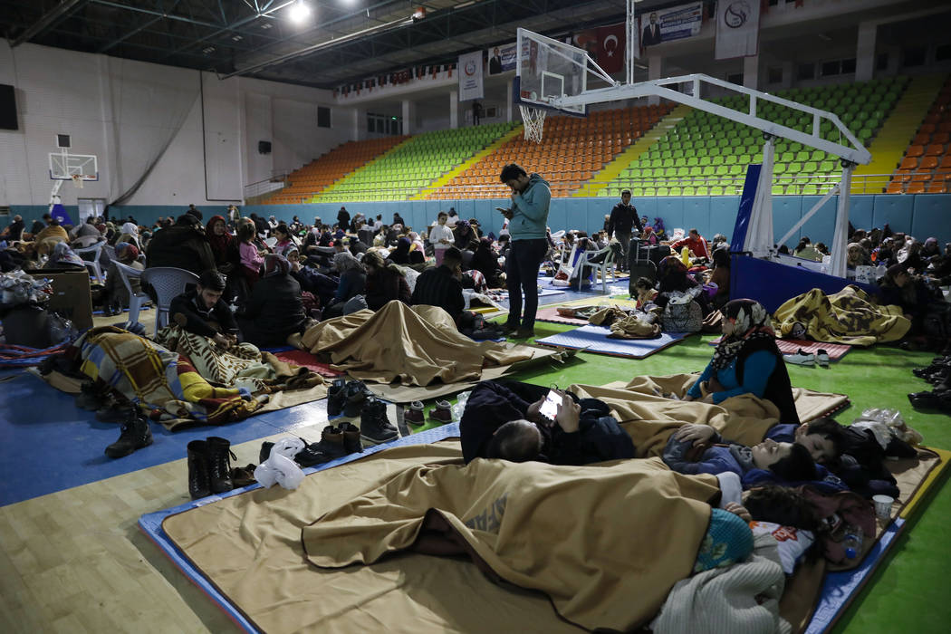 People gather inside a sports hall to spend the night following Friday's earthquake that destro ...