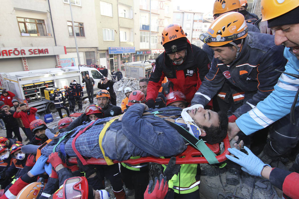 Rescue workers carry a wounded man that was found alive in the rubble of a building destroyed o ...