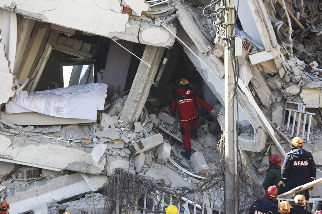 Rescuers work on searching for people buried under the rubble on a collapsed building, after an ...