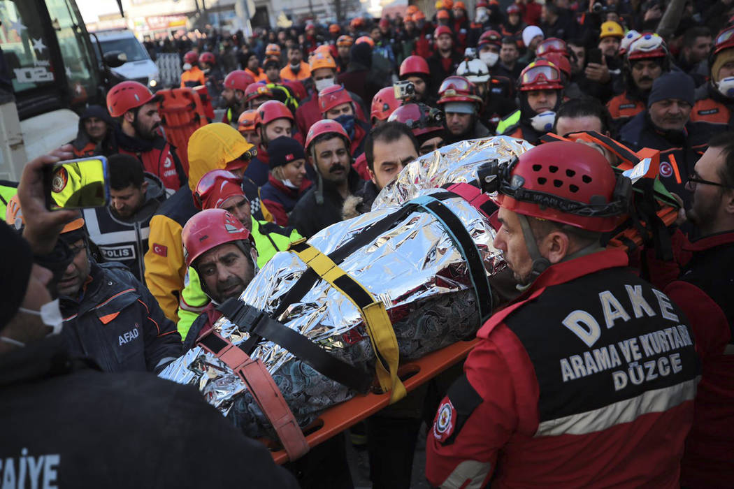 Members of rescue services carry a wounded man, that was found in the rubble of a building dest ...