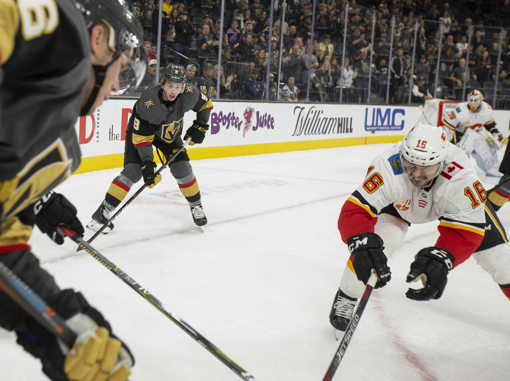 Golden Knights center Cody Glass (9) eyes the puck as Calgary Flames center Tobias Rieder (16) ...