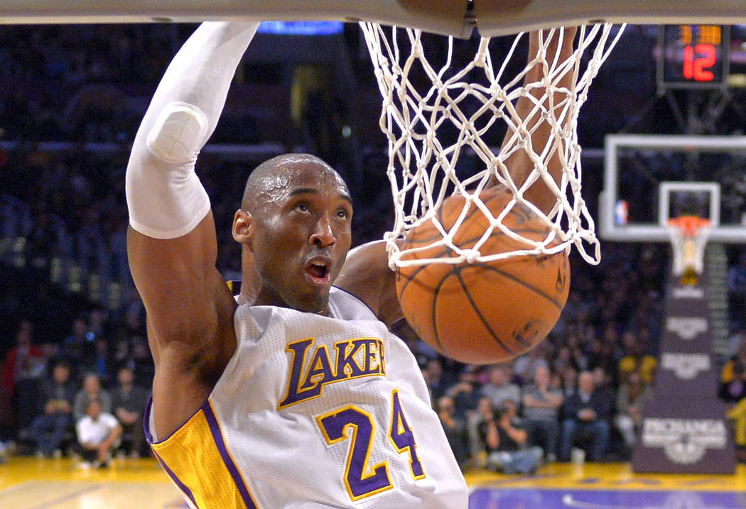 FILE - In this Jan. 4, 2015 file photo Los Angeles Lakers guard Kobe Bryant dunks during the fi ...