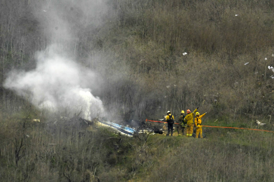 Firefighters work the scene of a helicopter crash where former NBA star Kobe Bryant died, Sunda ...