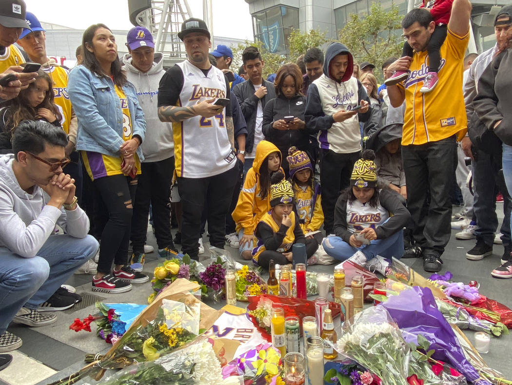 Fan gather around make shift memorials as they mourn the loss of Kobe Bryant in front of La Liv ...