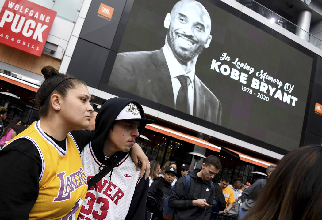 Fans mourn the loss of Kobe Bryant in front of La Live across from Staples Center, home of the ...
