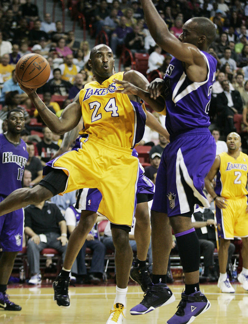 Los Angeles Lakers basketball star Kobe Bryant (24) looks to pass around Sacramento Kings playe ...