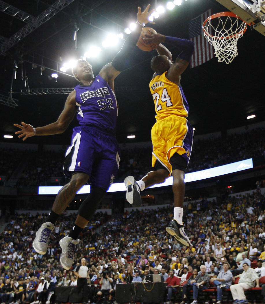 Kobe Bryant (24) of the Los Angeles Lakers goes in for a dunk past the Sacramento Kings' James ...