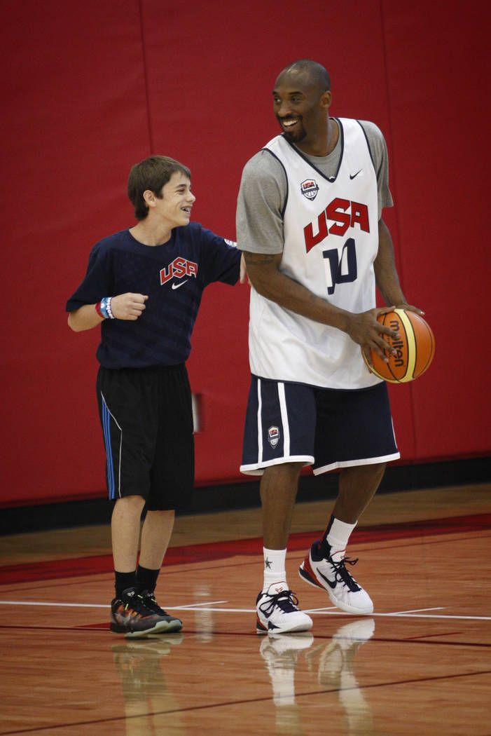 2012 USA Basketball Men's National Team player Kobe Bryan, right, shoots with a young man durin ...