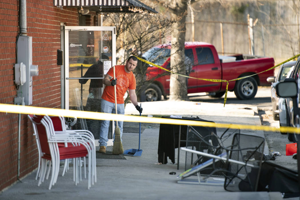 A man cleans up in front of Mac's Lounge, the scene of an early morning bar shooting, Sunday, J ...