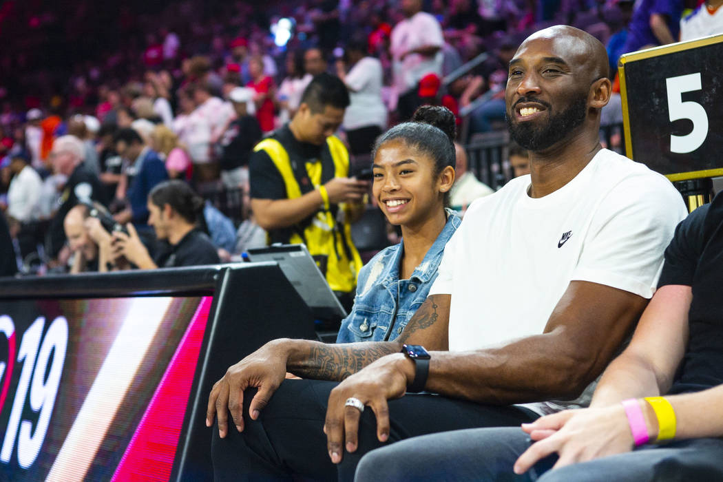 NBA legend Kobe Bryant sits with his daughter, Gianna, before the start of the WNBA All-Star Ga ...