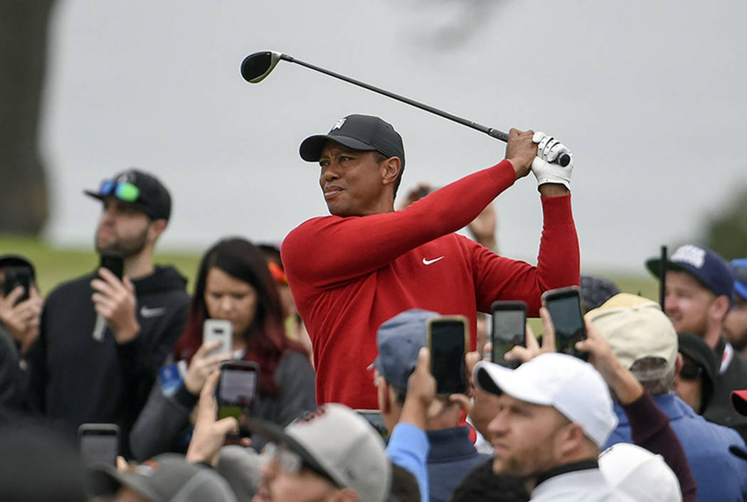 Tiger Woods watches his tee shot on the second hole of the South Course at Torrey Pines Golf Co ...