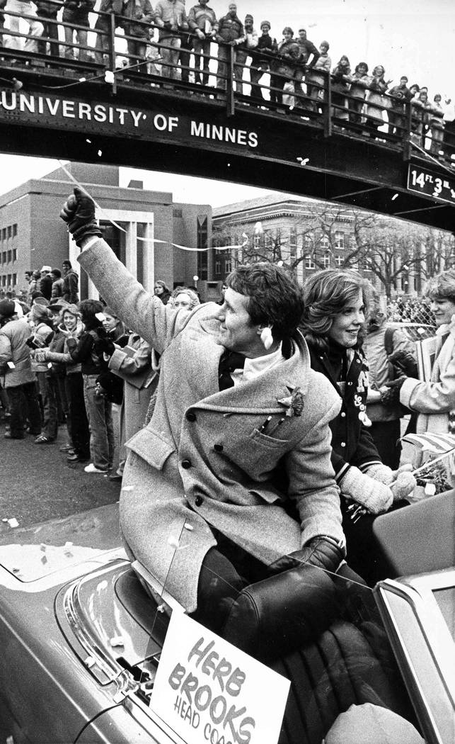 Olympic hockey coach Herb Brooks waves to the crowd as confetti flies in Minneapolis, Feb. 27, ...