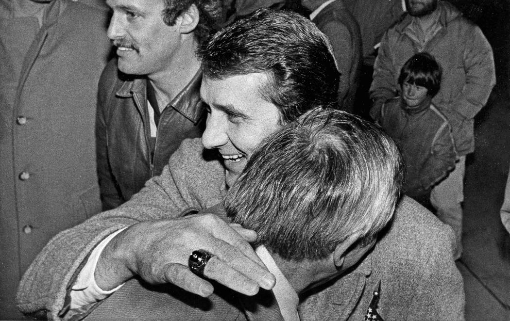 U.S. Olympic hockey coach Herb Brooks gives a hugs to University of Minnesota athletic director ...