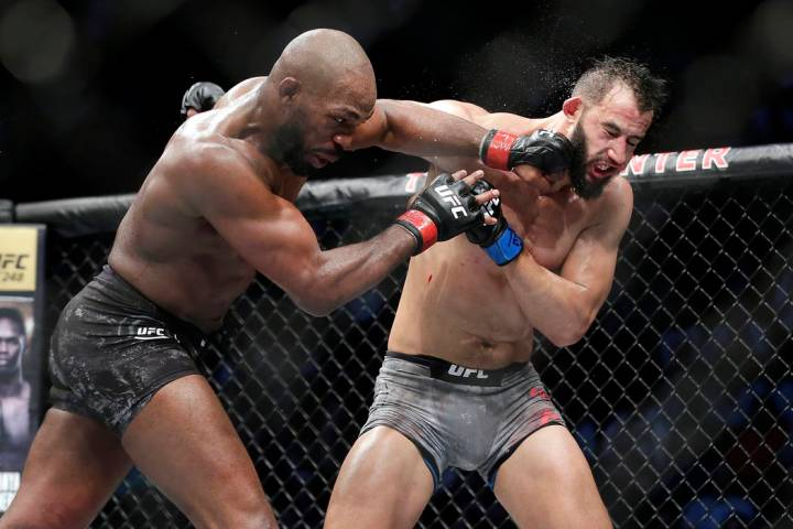 Jon Jones, left, connects with a punch to the face of Dominick Reyes, right, during a light hea ...
