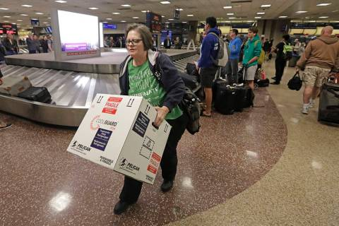 Ann Lovell carries her box of prescriptions after returning to Salt Lake City International Air ...
