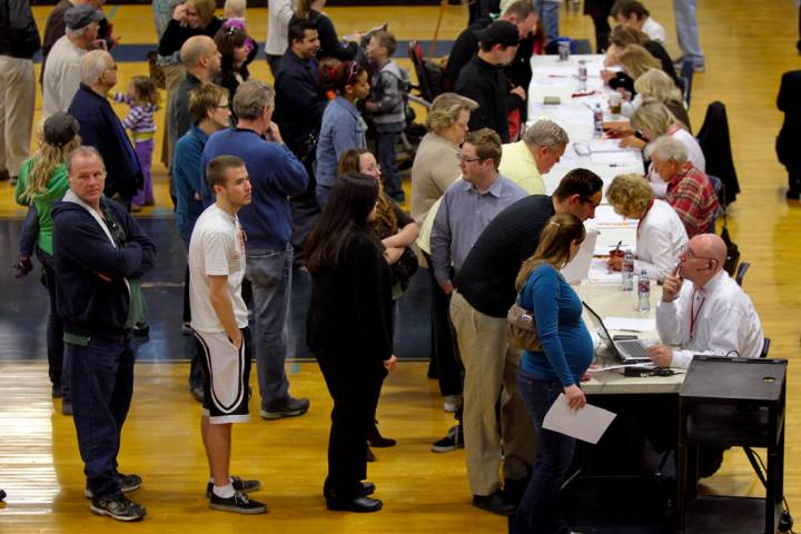 Voters wait to be check in at the voter verification station during the Republican caucus at Ce ...