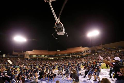 Fans rush to collect a piece of the $5,000 dropped from a helicopter at half time during an USL ...