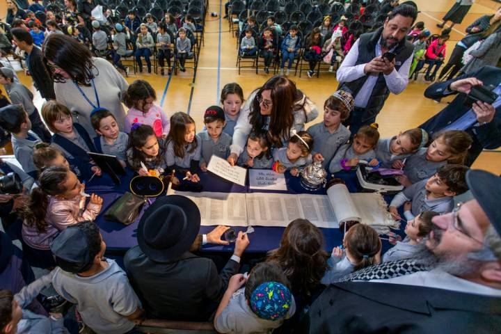 Rabbi Dovid Bressman, bottom left, as Sofer readies to inscribe the new Torah surrounded by fir ...