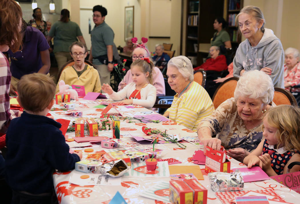 Katerina Smith, 4, right, and Elise Adoor, 5, center, make a Valentine's Day themed craft with ...