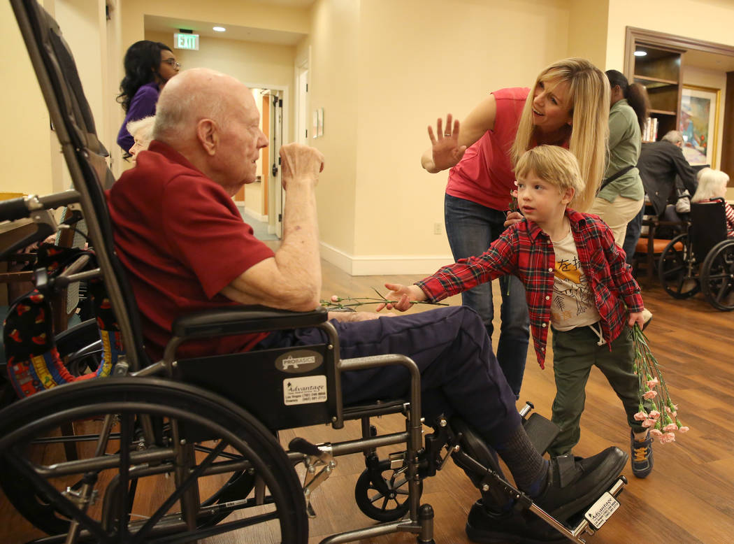 Jack Jones, 4, hands out Valentine's flowers to Jeff Nichol as his mother Jenny looks on at Poe ...