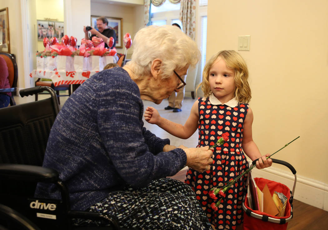 Katerina Smith, 4, hands out Valentine's flowers to Erika Totera at Poet's Walk, a memory care ...
