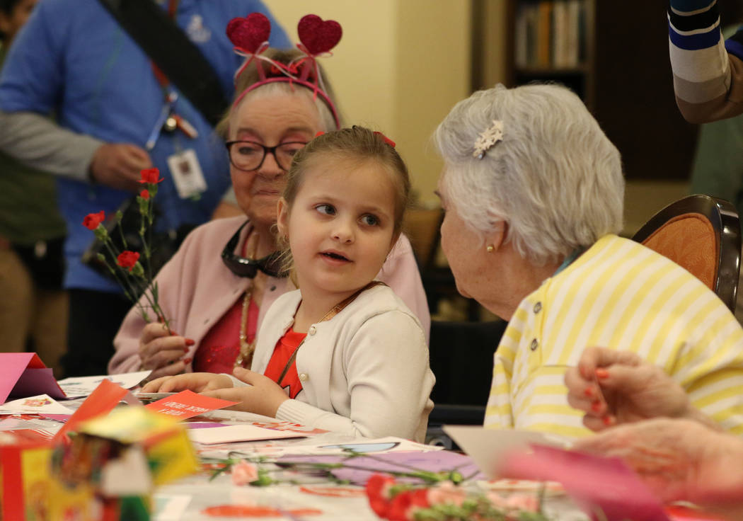 Elise Adoor, 5, center, makes a Valentine's Day themed craft with Barbara Wokosky, left, and Ma ...