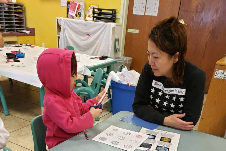 Fumika Takayama, working with her youngest child on labeling the solar system on Feb. 6, has ta ...