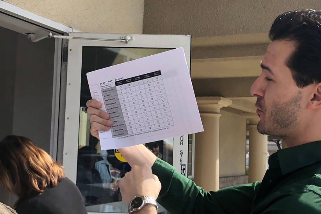 A poll worker explains the paper ballot with those waiting in line at 3511 E. Harmon Ave. on Su ...