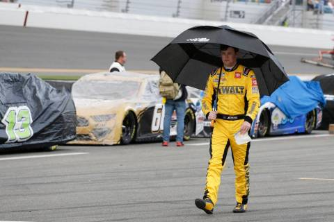 Erik Jones walks down pit road after rain caused a delay in the NASCAR Daytona 500 auto race at ...