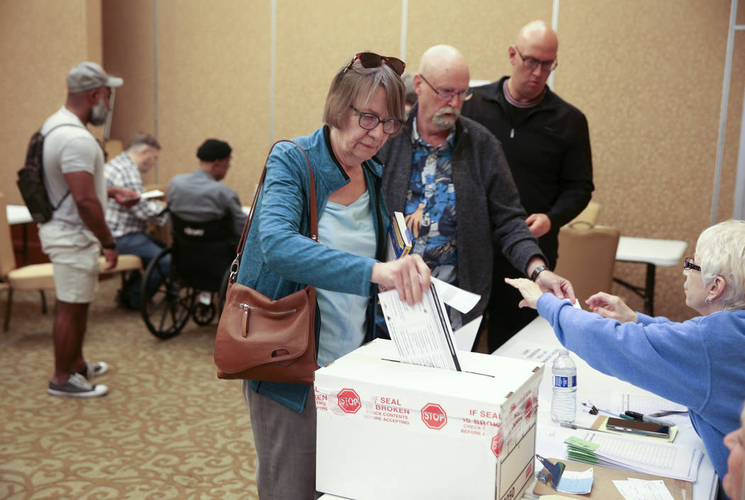 Leslie Doughman, 64, of Henderson, drops her ballot in the box during early voting in the Nevad ...