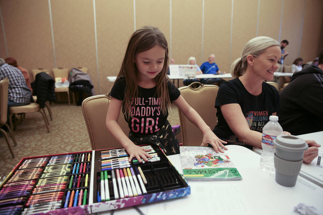 Madden Johlfs, 5, colors while her mother Susan Johlfs, 49, checks in for early voting in the N ...