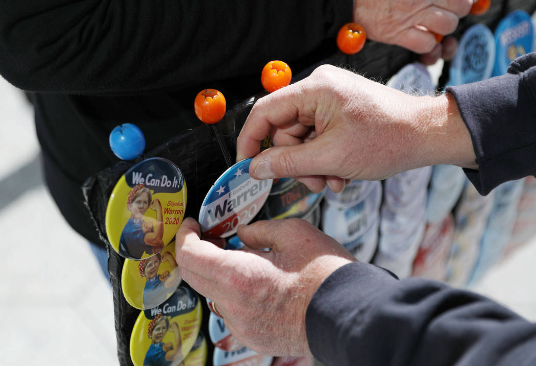 A Sen. Elizabeth Warren supporter purchases a pin before Warren speaks ahead of a town hall at ...