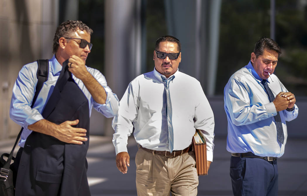 Counselor Mark Fleming, left, walks out with defendant Albert Lopez and past defendant Bradley ...