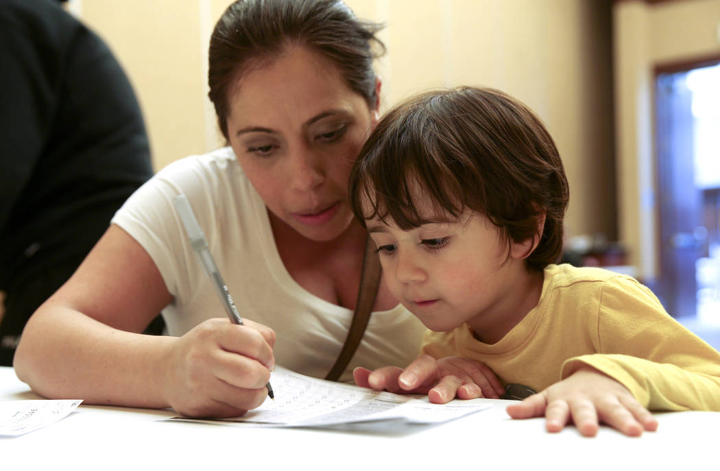 Alexander Silva, 3, of Henderson watches his mother Marcela fill out her ballot during early vo ...