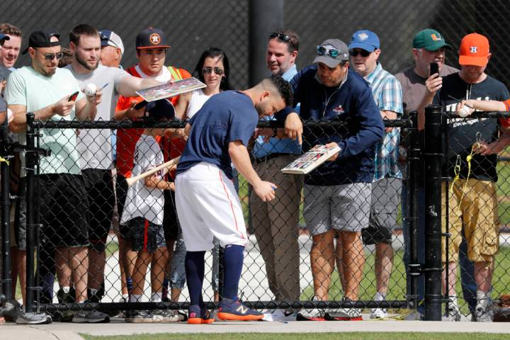 Houston Astros' Jose Altuve signs autographs during spring training baseball practice Thursday, ...