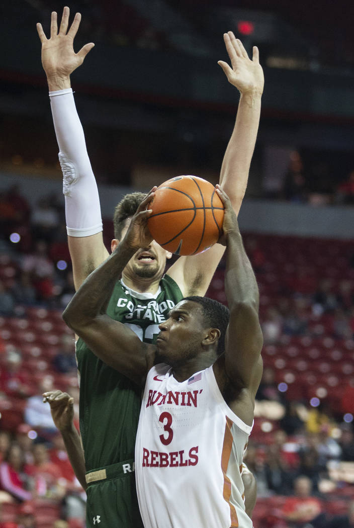 UNLV Rebels guard Amauri Hardy (3) drives past Colorado State Rams center Nico Carvacho (32) in ...