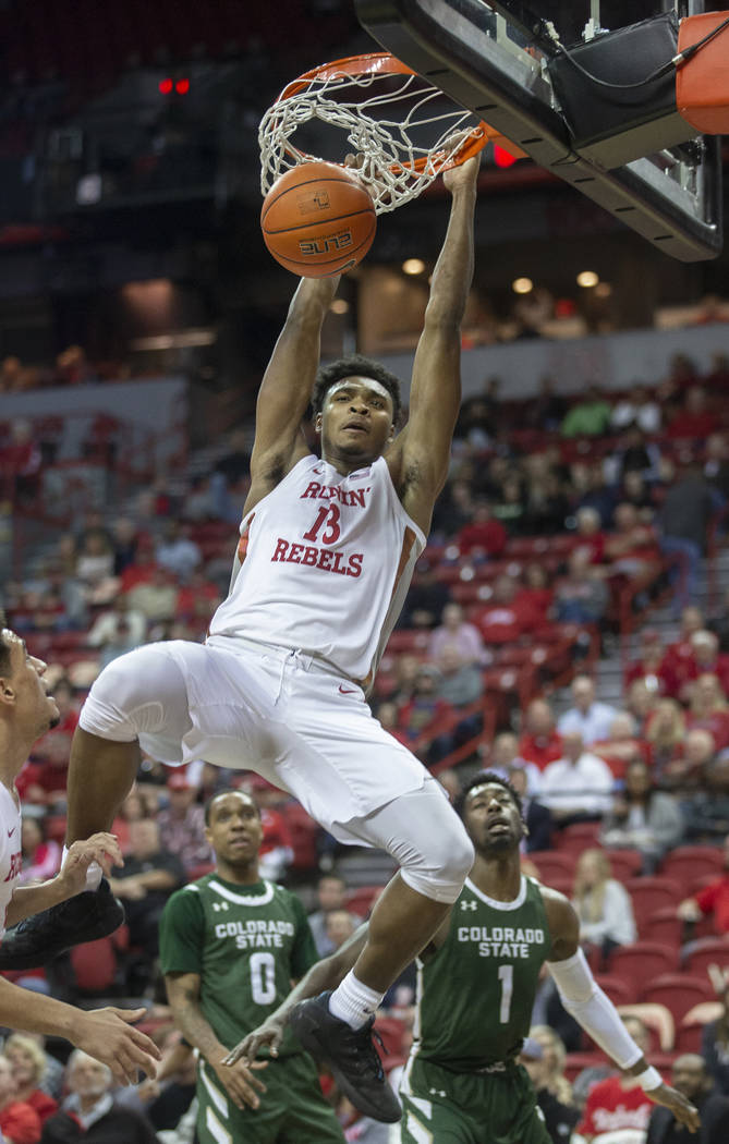 UNLV Rebels guard Bryce Hamilton (13) dunks over Colorado State Rams guard Kris Martin (1) and ...