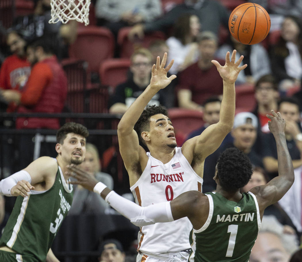 UNLV Rebels guard Jay Green (0) fights for a rebound with Colorado State Rams guard Kris Martin ...