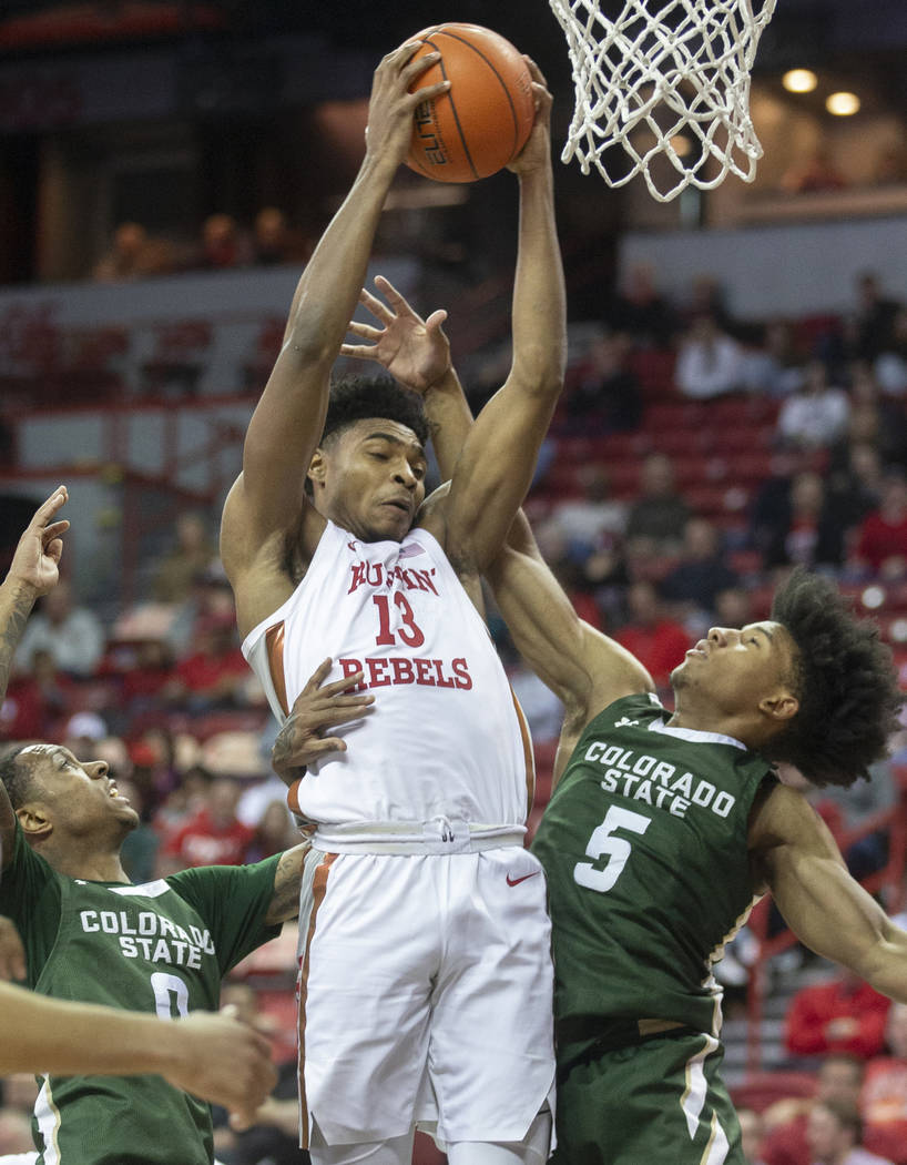 UNLV Rebels guard Bryce Hamilton (13) grabs a rebound over Colorado State Rams guard P.J. Byrd ...