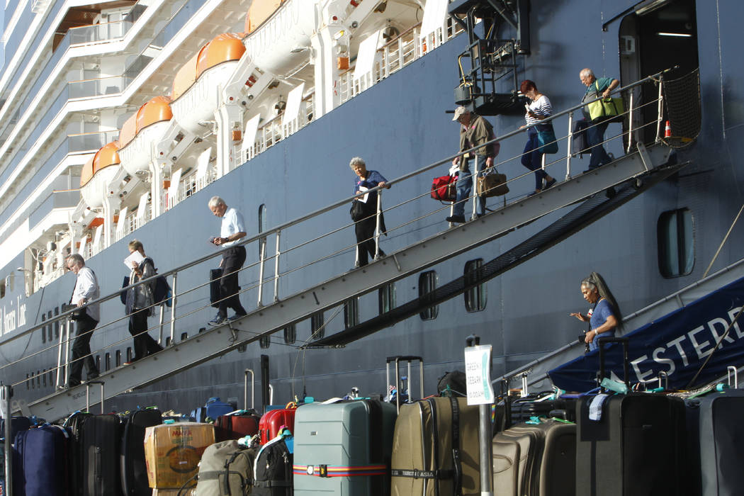Passengers of the MS Westerdam, back, owned by Holland America Line, disembark at the port of S ...